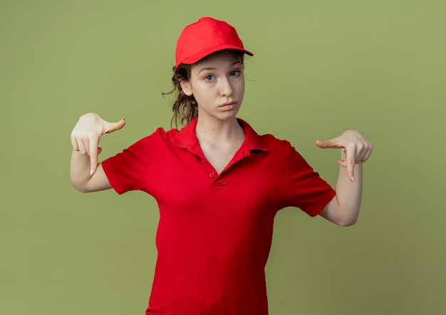 Onder de indruk jong mooi bezorgmeisje in rood uniform en pet naar beneden geïsoleerd op olijfgroene achtergrond met kopie ruimte