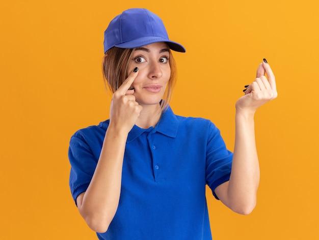 Onder de indruk jong mooi bezorgmeisje in uniform trekt ooglid naar beneden en gebaren geld handteken op oranje