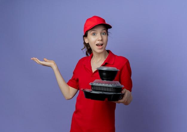 Onder de indruk jong mooi leveringsmeisje die rood uniform en glb dragen die voedselcontainers houden die lege hand tonen die op purpere achtergrond met exemplaarruimte wordt geïsoleerd