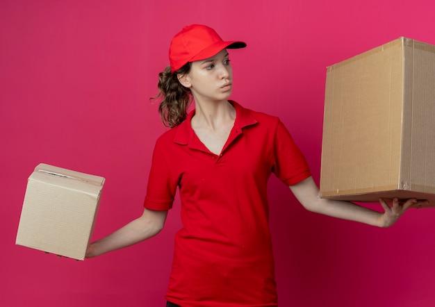 Onder de indruk jong mooi leveringsmeisje in rood uniform en glb die kartondozen houden die kant bekijken die op karmozijnrode achtergrond wordt geïsoleerd