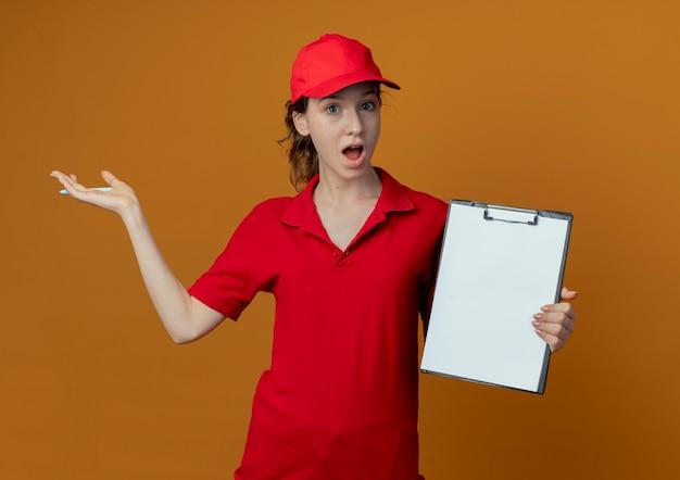 Onder de indruk jong mooi leveringsmeisje in rood uniform en glb die pen en klembord houden en met hand aan kant richten die op oranje achtergrond wordt geïsoleerd