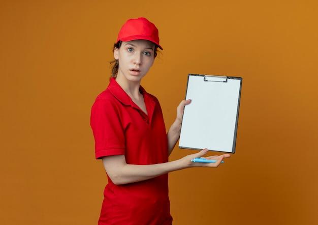 Onder de indruk jong mooi leveringsmeisje in rood uniform en glb die pen houden en klembord tonen dat op oranje achtergrond met exemplaarruimte wordt geïsoleerd