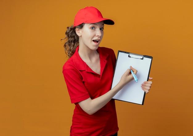 Onder de indruk jong mooi leveringsmeisje in rood uniform en glb-holdingspen en klembord die camera bekijken die op oranje achtergrond met exemplaarruimte wordt geïsoleerd