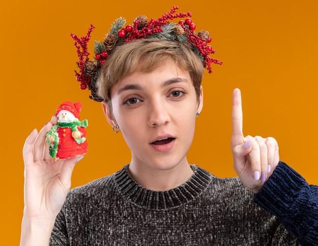 Onder de indruk jong mooi meisje die de hoofdkroon van kerstmis dragen die klein standbeeld van de kerstmissneeuwman houdt die camera bekijkt die omhoog wijst geïsoleerd op oranje achtergrond