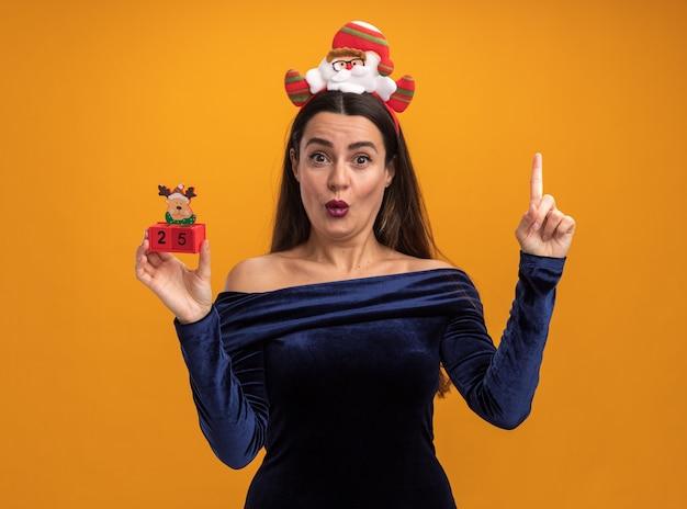 Onder de indruk jong mooi meisje draagt blauwe jurk en kerst haar hoepel bedrijf speelgoed wijst naar boven geïsoleerd op een oranje achtergrond