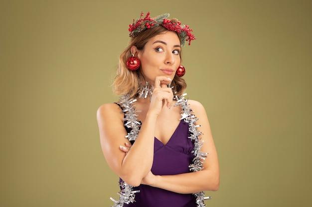 Onder de indruk jong mooi meisje draagt paarse jurk en krans met guirlande op nek met kerstballen op oren pakte kin geïsoleerd op olijf groene achtergrond