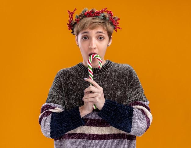 Onder de indruk jong mooi meisje dragen kerst hoofd krans houden kerst zoete suikerriet klaar om te eten kijken camera geïsoleerd op een oranje achtergrond
