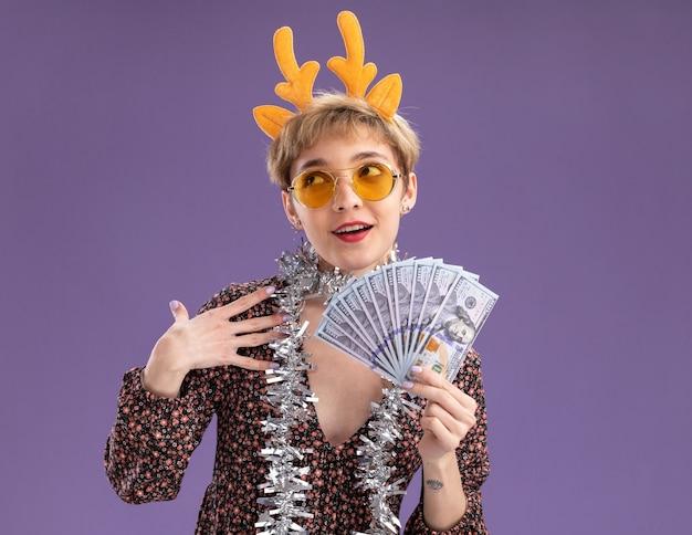 Onder de indruk jong mooi meisje dragen rendiergeweien hoofdband en klatergoud slinger rond de nek met bril houden geld opzoeken aanraken schouder geïsoleerd op paarse achtergrond