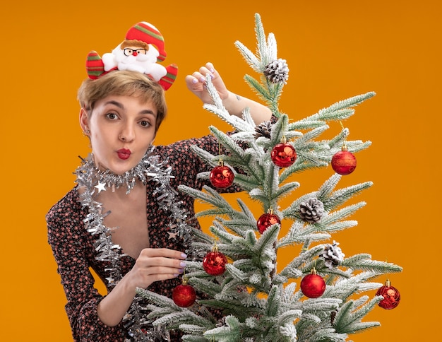 Onder de indruk jong mooi meisje met de hoofdband van de kerstman en klatergoudslinger om de nek die achter de versierde kerstboom staat en het aanraakt en kusgebaar doet geïsoleerd op een oranje muur