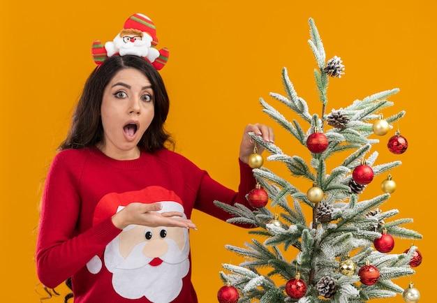 Onder de indruk jong mooi meisje met hoofdband van de kerstman en trui staande in de buurt van de kerstboom die het versieren kijkend naar de camera wijzend op boom geïsoleerd op een oranje achtergrond