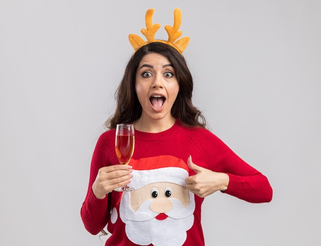 Onder de indruk jong mooi meisje met rendiergeweien hoofdband en kerstman trui met glas champagne op zoek duim opdagen