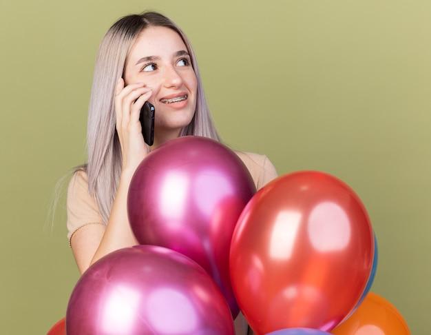 Onder de indruk jong mooi meisje met tandheelkundige beugels spreekt op de telefoon die achter ballonnen staat geïsoleerd op een olijfgroene muur