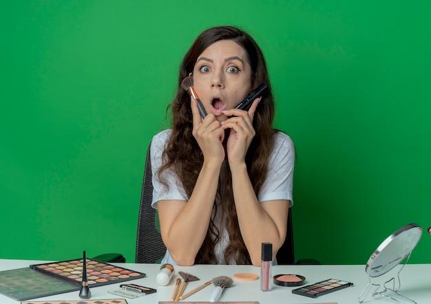 Onder de indruk jong mooi meisje zit aan de make-up tafel met make-up tools blozen en poeder borstels te houden en het aanraken van gezicht met hen geïsoleerd op groene achtergrond