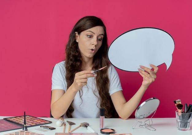 Onder de indruk jong mooi meisje zit aan de make-up tafel met make-up tools houden praatjebel en oogschaduw borstel en kijken naar borstel geïsoleerd op karmozijnrode achtergrond