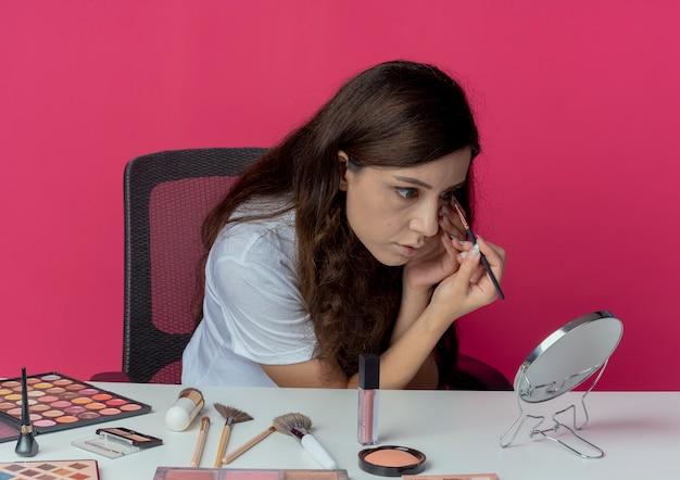 Onder de indruk jong mooi meisje zit aan de make-up tafel met make-up tools spiegel aanraken gezicht kijken en oogschaduw met make-up borstel geïsoleerd op crimson achtergrond toe te passen