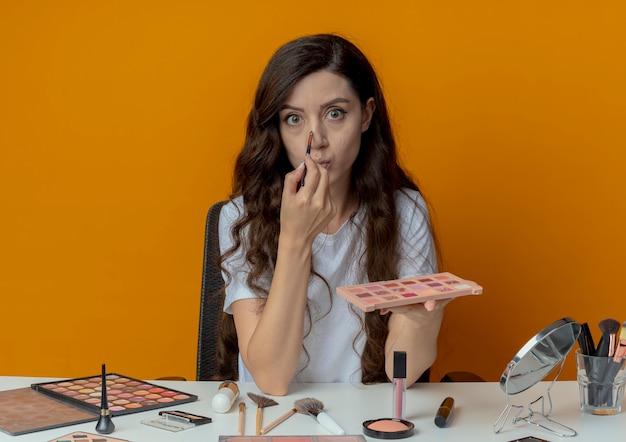 Onder de indruk jong mooi meisje zit aan de tafel van de make-up met make-up tools houden oogschaduw palet en aanraken neus met oogschaduw borstel geïsoleerd op een oranje achtergrond