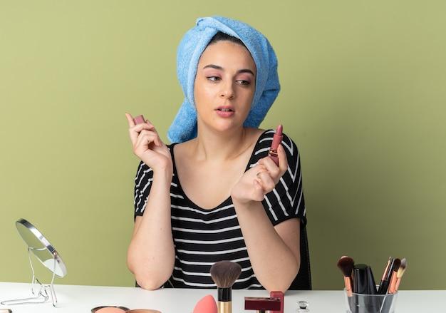 Onder de indruk jong mooi meisje zit aan tafel met make-up tools gewikkeld haar in handdoek vasthouden en kijken naar lippenstift geïsoleerd op olijfgroene muur