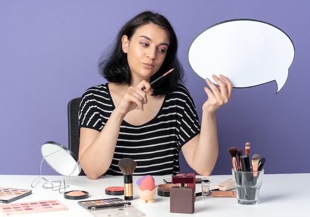Onder de indruk jong mooi meisje zit aan tafel met make-up tools met tekstballon met make-up borstel geïsoleerd op blauwe muur