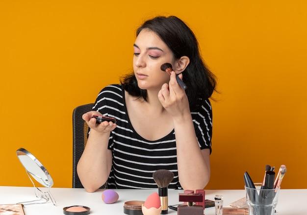 Onder de indruk jong mooi meisje zit aan tafel met make-uptools die poederblush toepassen geïsoleerd op een oranje muur
