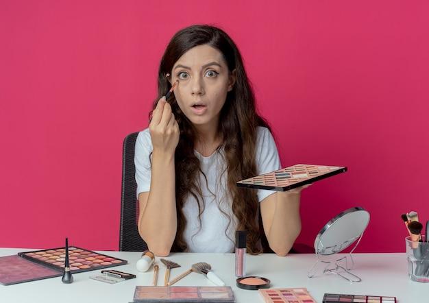 Onder de indruk jong mooi meisje zittend aan de make-up tafel met make-up tools oogschaduw palet houden en oogschaduw toe te passen met oogschaduw borstel geïsoleerd op crimson achtergrond