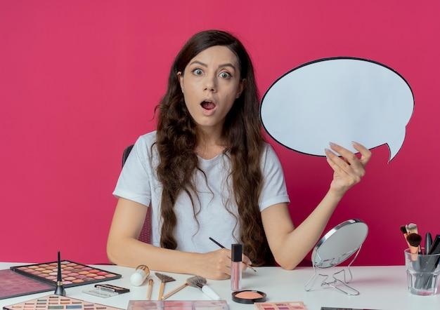 Onder de indruk jong mooi meisje zittend aan make-up tafel met make-up tools praatje bubble en oogschaduw borstel geïsoleerd op een karmozijnrode achtergrond te houden