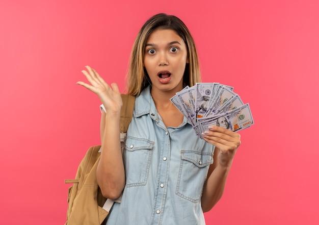 Onder de indruk jong mooi studentenmeisje die achterzak dragen die geld houdt en lege hand toont die op roze wordt geïsoleerd