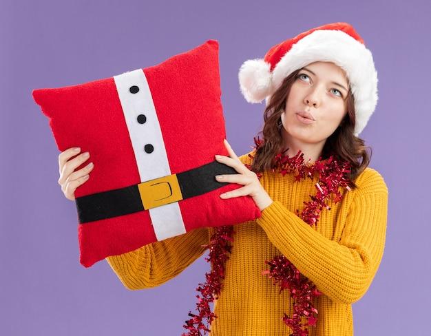 Onder de indruk jong slavisch meisje met kerstmuts en met slinger rond nek houden versierd kussen opzoeken geïsoleerd op paarse achtergrond met kopie ruimte