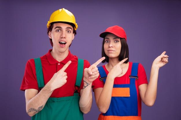 Onder de indruk jong stel in een bouwvakker uniforme man met een veiligheidshelm meisje met een pet die naar de zijkant wijst