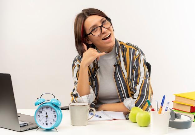 Onder de indruk jong studentenmeisje die glazen dragen die aan bureau zitten die roepnaam doen die op wit wordt geïsoleerd