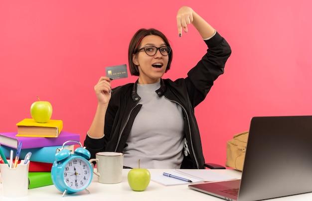Onder de indruk jong studentenmeisje die glazen dragen die aan bureau zitten met creditcard die naar beneden wijst die huiswerk doen dat op roze wordt geïsoleerd