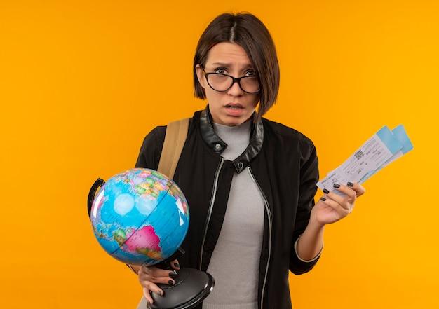 Onder de indruk jong studentenmeisje die glazen en rugtas dragen die vliegtuigtickets en bol houden die op oranje worden geïsoleerd