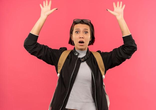 Onder de indruk jong studentenmeisje die glazen op hoofd en achterzak dragen die handen opheffen die op roze worden geïsoleerd