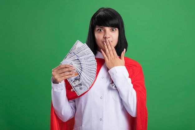 Onder de indruk jong superheldmeisje die stethoscoop met medisch kleed en mantel dragen die contant geld en behandelde mond met hand houden die op groene muur wordt geïsoleerd