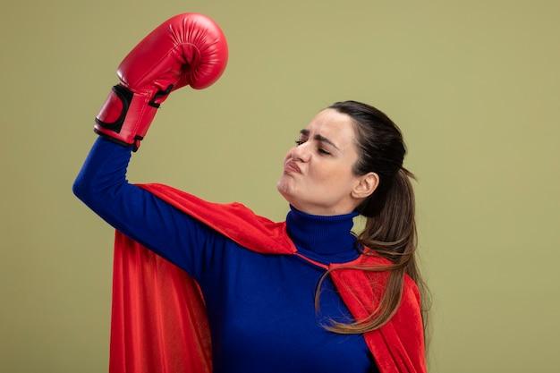 Onder de indruk jong superheromeisje die bokshandschoenen dragen die sterk gebaar tonen dat op olijfgroen wordt geïsoleerd