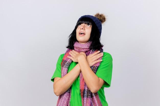 Onder de indruk jong ziek kaukasisch meisje die de winterhoed en sjaal dragen die omhoog het houden handen op schouders kruisen die op witte achtergrond met exemplaarruimte worden geïsoleerd