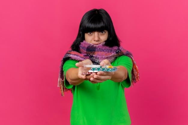 Onder de indruk jong ziek kaukasisch meisje dragen sjaal kijken camera en strekken spuit en medische pillen naar camera geïsoleerd op crimson achtergrond met kopie ruimte