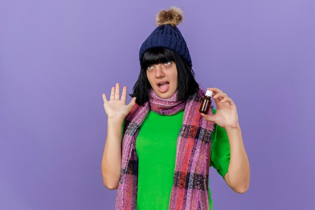 Onder de indruk jong ziek kaukasisch meisje dragen winter hoed en sjaal geneesmiddel in glas houden met lege hand opzoeken geïsoleerd op paarse achtergrond met kopie ruimte