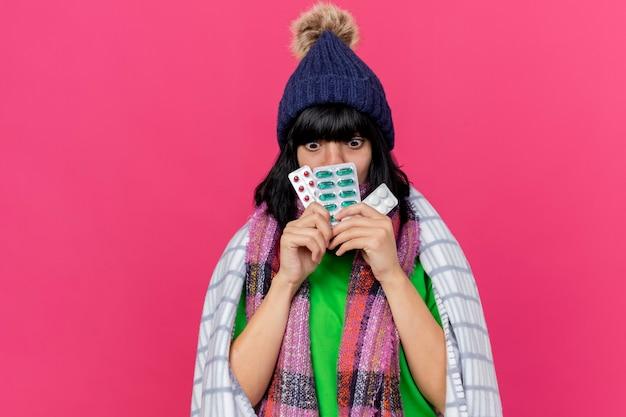 Onder de indruk jong ziek kaukasisch meisje dragen winter hoed en sjaal verpakt in plaid bedrijf verpakkingen van medische pillen voor mond neerkijkt geïsoleerd op karmozijnrode achtergrond met kopie ruimte