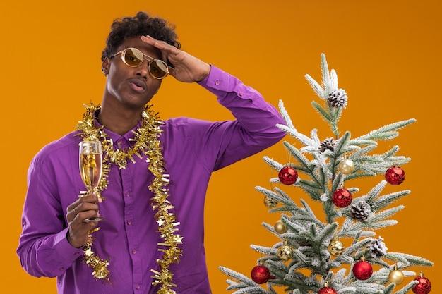 Onder de indruk jonge afro-amerikaanse man met bril met klatergoud slinger rond de nek staande in de buurt van versierde kerstboom met glas champagne