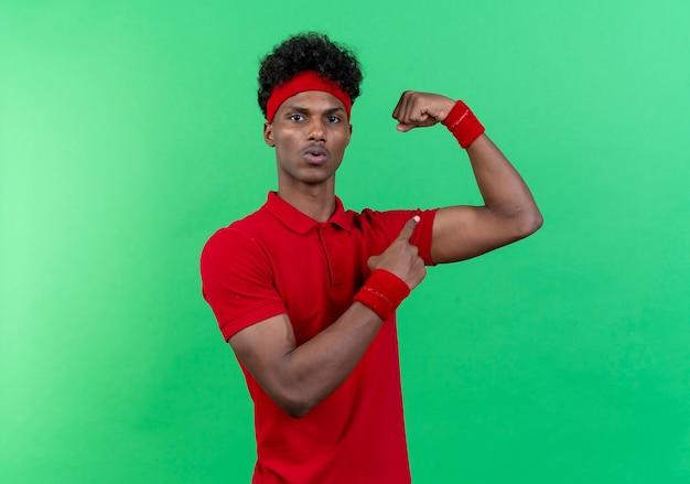 Onder de indruk jonge afro-amerikaanse sportieve man met hoofdband en polsbandje doet sterk gebaar en punten geïsoleerd op een groene achtergrond