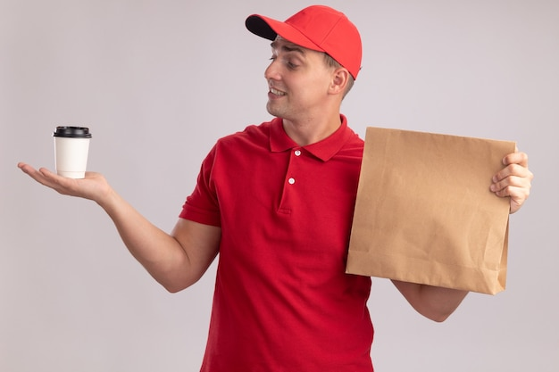 Onder de indruk jonge bezorger die uniform met pet draagt die papier voedselpakket vasthoudt en naar een kopje koffie kijkt in zijn hand geïsoleerd op een witte muur