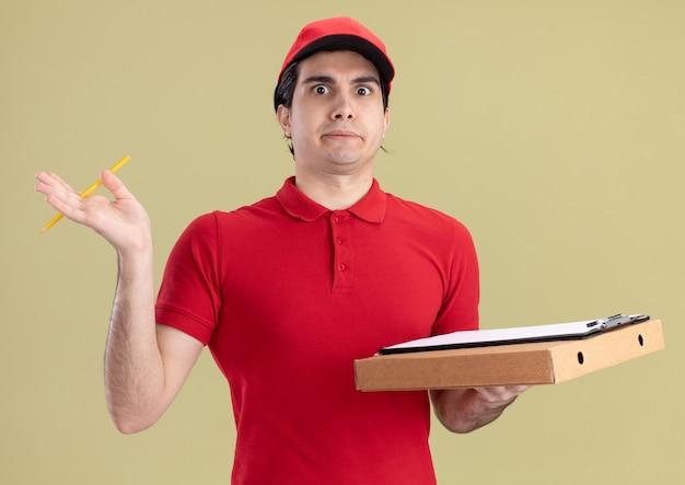 Onder de indruk jonge bezorger in rood uniform en pet met pizzapakket klembord en potlood kijkend naar voorkant geïsoleerd op olijfgroene muur
