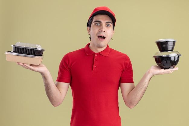Onder de indruk jonge bezorger in rood uniform en pet met voedselcontainers en papieren voedselpakket kijkend naar voorkant geïsoleerd op olijfgroene muur
