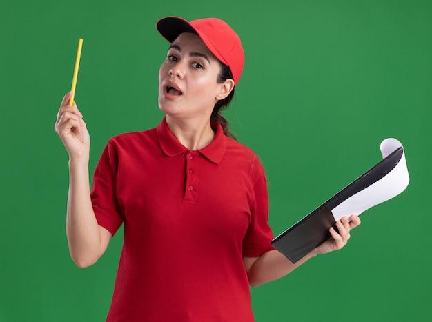 Onder de indruk jonge bezorger in uniform en pet met klembord en potlood kijkend naar de voorkant geïsoleerd op de muur
