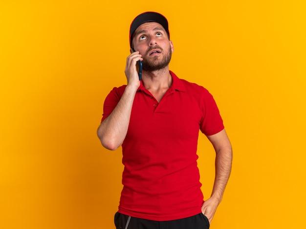 Onder de indruk jonge blanke bezorger in rood uniform en pet die hand in zak houdt terwijl hij aan de telefoon praat en omhoog kijkt geïsoleerd op oranje muur met kopieerruimte