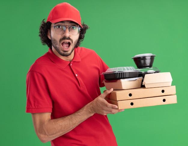 Onder de indruk jonge blanke bezorger in rood uniform en pet met bril met pizzapakketten met papieren voedselpakketten en voedselcontainers erop