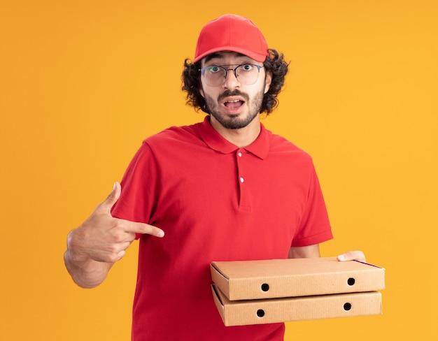 Onder de indruk jonge blanke bezorger in rood uniform en pet met een bril die pizzapakketten vasthoudt en wijst