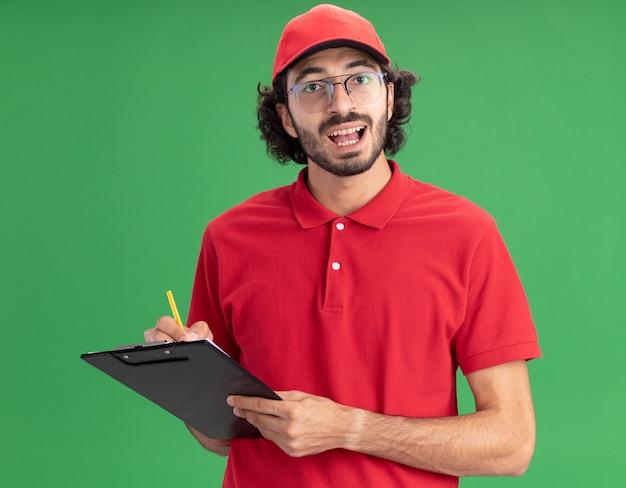 Onder de indruk jonge blanke bezorger in rood uniform en pet met een bril met klembord en potlood