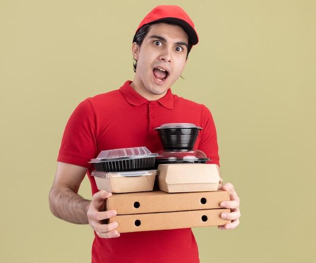 Onder de indruk jonge blanke bezorger in rood uniform en pet met pizzapakketten met voedselcontainers en papieren voedselpakketten erop geïsoleerd op olijfgroene muur