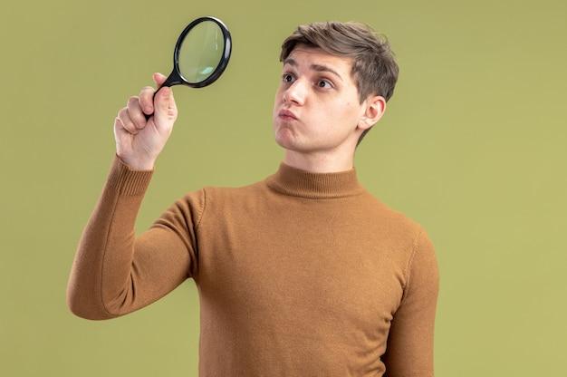 Onder de indruk jonge blanke jongen die vergrootglas vasthoudt en bekijkt